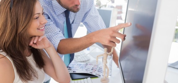 Man pointing something to his partner on screen in creative office